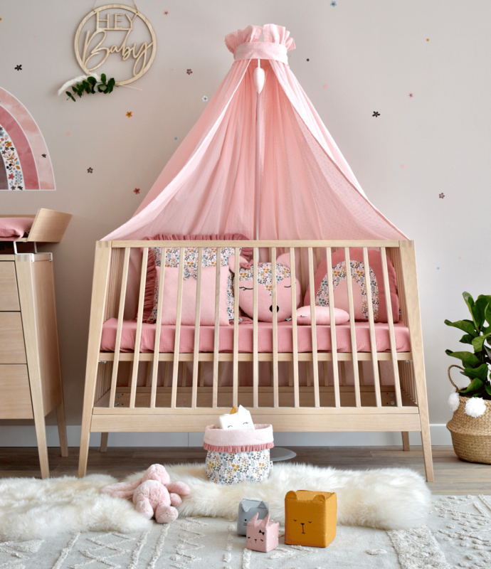 Baby room with flowery textiles & wooden furniture
